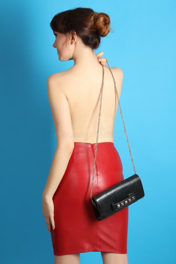 Яркая красная юбка и черная малая сумка стоковое фото rf