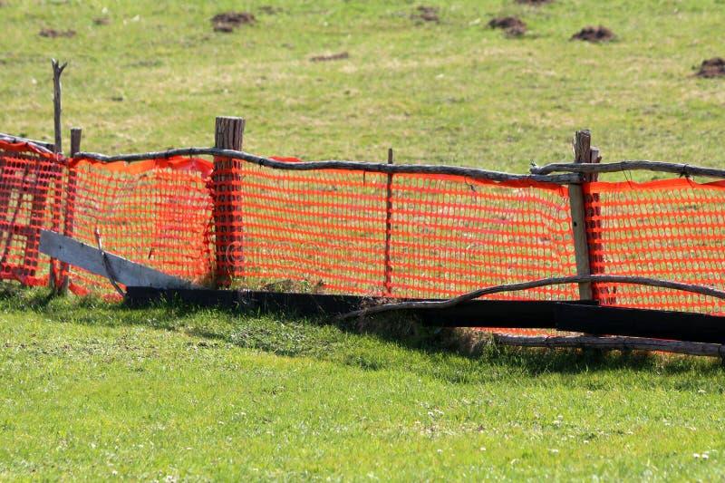 Яркая оранжевая временная сымпровизированная загородка сделанная из сети нейлона и деревянных поляков окруженных с uncut травой и стоковая фотография rf