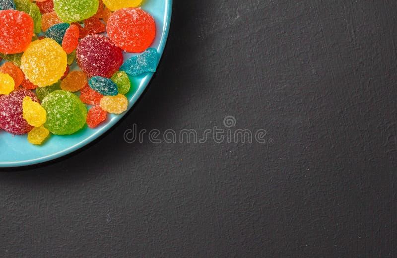 Яркая покрашенная конфета, мармелад, помадки в голубой плите на темной предпосылке стоковые фото