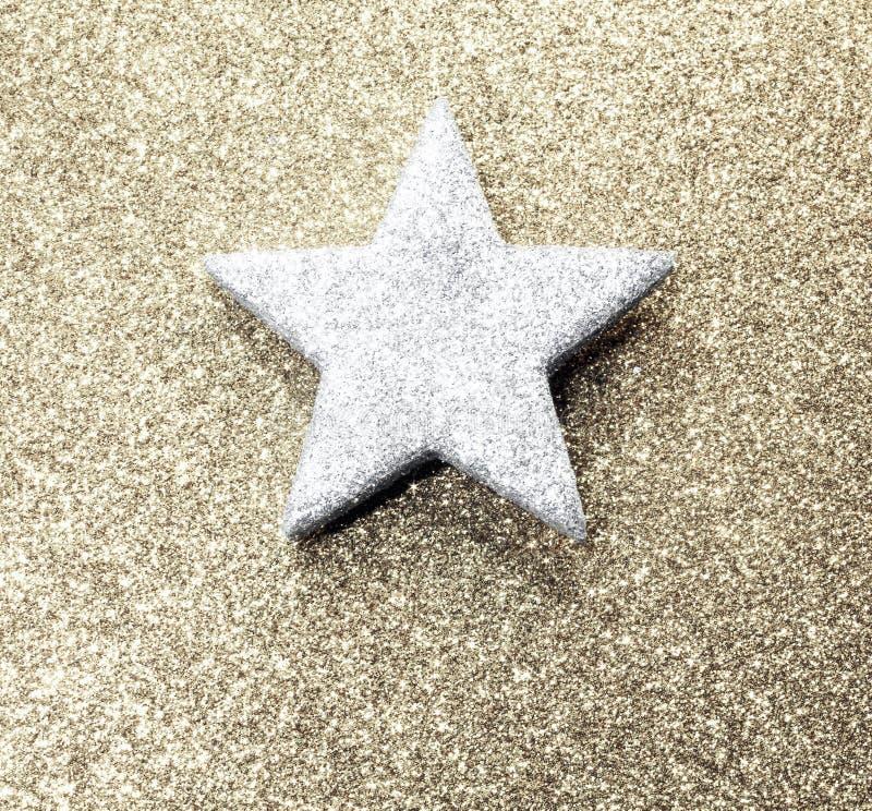 Яркая серебряная звезда на золотой сияющей предпосылке стоковые изображения rf