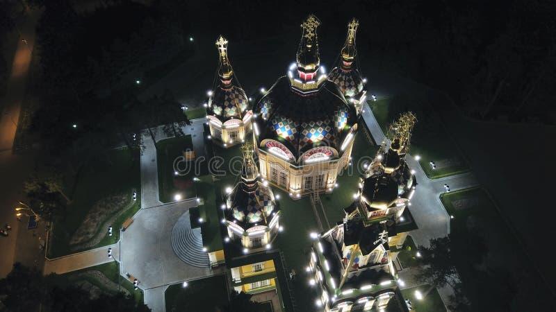 Яркая церковь с золотыми куполами и крестами Накаляет в парке ночи E стоковые изображения