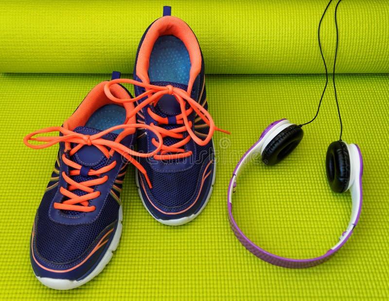 Яркие ботинки и наушники на свернутой циновке йоги стоковая фотография