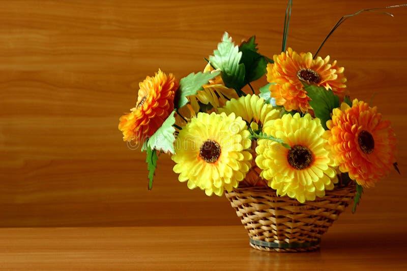 Яркие декоративные искусственные цветки в сплетенной корзине для вашего рабочего стола стоковые изображения