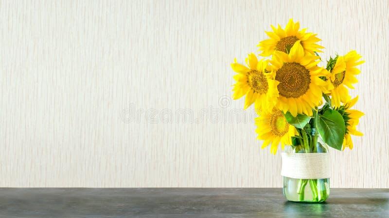Яркие желтые большие солнцецветы в стеклянной вазе на темной таблице на ligh стоковое фото rf