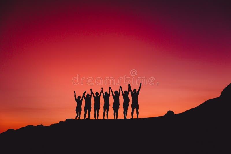 Яркие заход солнца или восход солнца и силуэт группы людей стоковое изображение