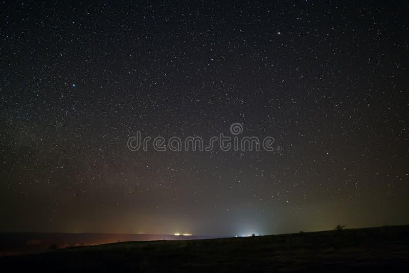 Яркие звезды в ночном небе с освещением от уличных фонарей города светлое загрязнение стоковая фотография rf