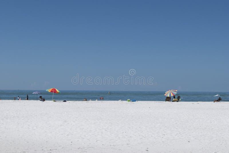 Яркие зонтики пляжа на белом песчаном пляже стоковые изображения rf