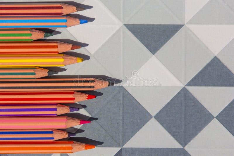 Яркие карандаши на современное низкое поли, предпосылка цвета полигона геометрическая абстрактная стоковые фото