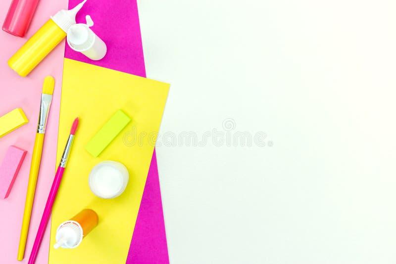 Яркие краски, щетки, ластики, покрасили бумагу альбома на белом ба стоковое фото