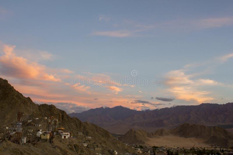 Яркие облака в голубом выравниваясь небе над домами на наклоне гор стоковое фото rf