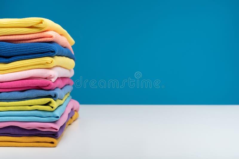 Яркие одежды лежа на таблице после мыть стоковые фотографии rf