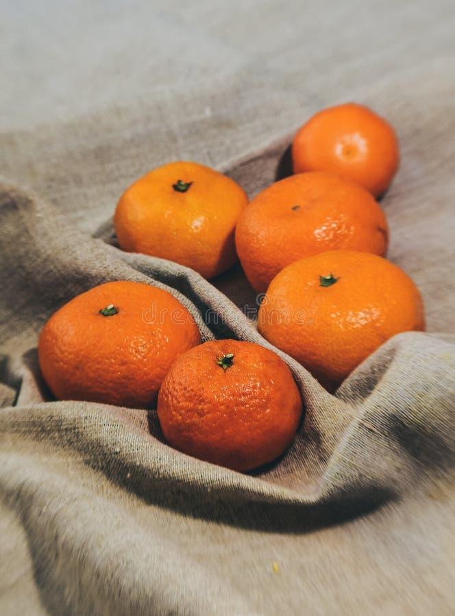 Яркие оранжевые tangerines на предпосылке ткани белья стоковое фото