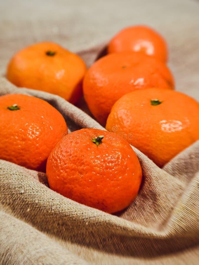 Яркие оранжевые tangerines на предпосылке ткани белья стоковые изображения rf