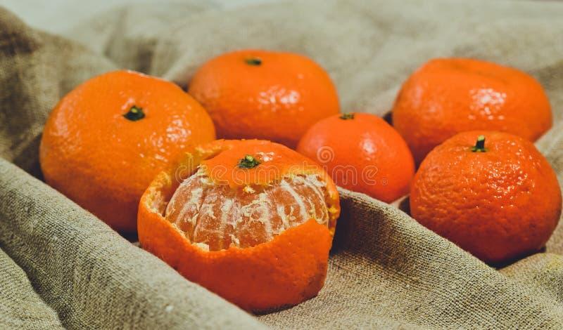 Яркие оранжевые tangerines на предпосылке ткани белья стоковая фотография