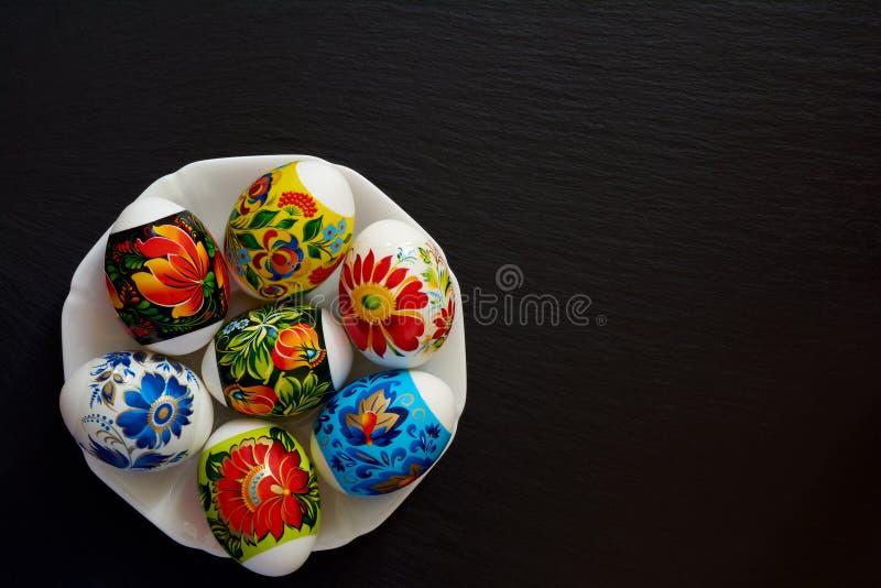 Яркие пестротканые пасхальные яйца с цветочным узором в плите на темной предпосылке Символ религиозного праздника стоковая фотография