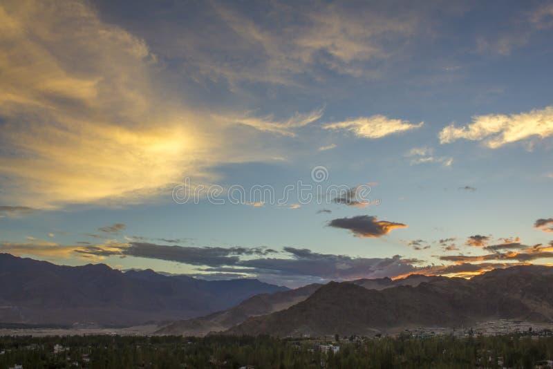 Яркие покрашенные облака в темно-синем небе во время захода солнца над городом в горах стоковое изображение