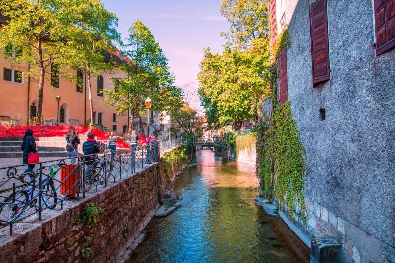 Яркие цвета Анси, Франции Туристы идут через дорогу около канала передачи зеленого цвета стоковые фотографии rf