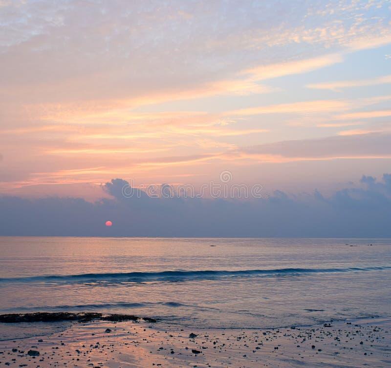 Яркие цвета в небе утра с золотыми желтыми линиями в облаках и красном Солнце поднимая на горизонт над океаном стоковое изображение rf