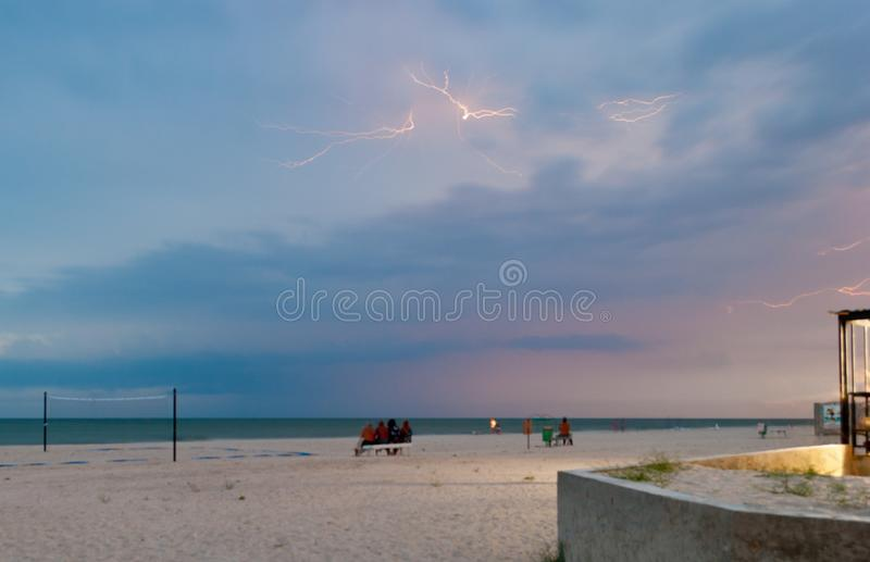 Яркий берег вечера молнии людей моря на стендах заволакивает небо захода солнца стоковая фотография rf