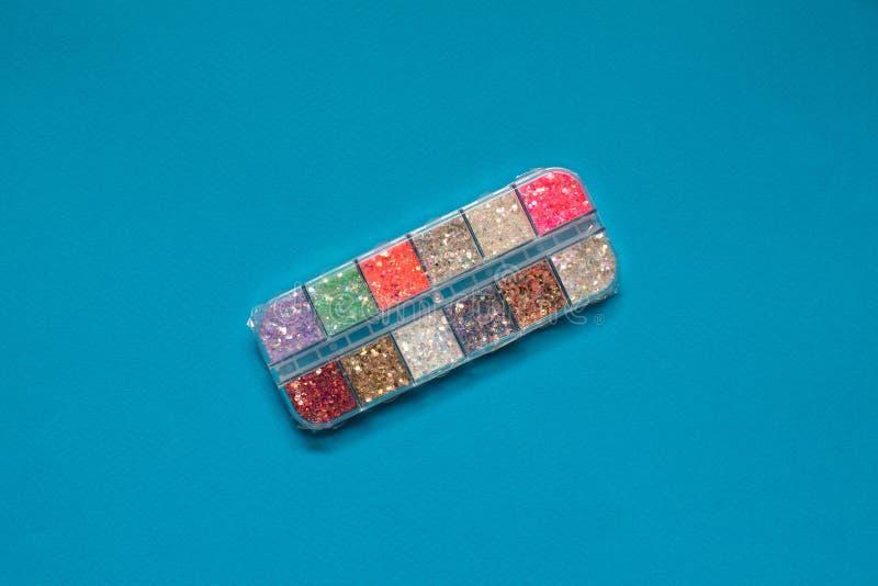 Красочные яркие блески для искусства и макияжа ногтя в небольшом контейнере на голубой предпосылке стоковые фото