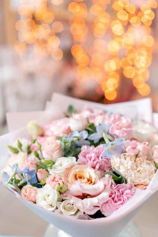Яркий букет смешанных цветков Флористический пук с голубым Delphinium в стеклянной вазе Bokeh гирлянды на предпосылке Рождество стоковая фотография