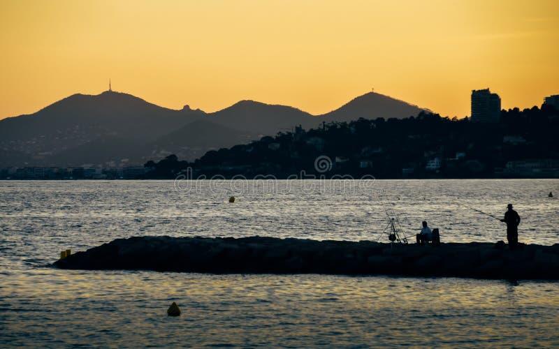 Яркий желтый заход солнца на пляже с заходом солнца в штырях les Хуана, ` Azur Коута d, Францией стоковое фото