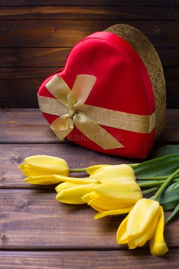 Яркий желтый цвет цветет тюльпаны и праздничная подарочная коробка в форме hea стоковая фотография rf