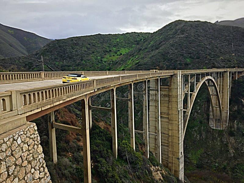 Яркий желтый Chevrolet Camaro быстро проходит через мост заводи Bixby, большое Sur, Калифорнию стоковые фотографии rf