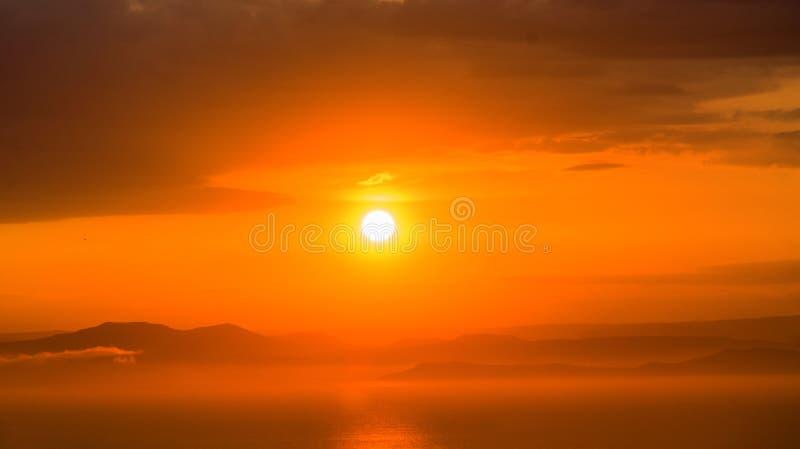 Яркий красный заход солнца над морем, после шторма Заход солнца шарлаха над водой и сериями облаков стоковые фотографии rf