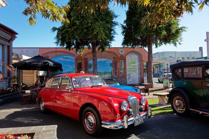 Яркий красный ягуар на винтажном шоу автомобиля в главной улице Motueka перед музеем стоковое фото