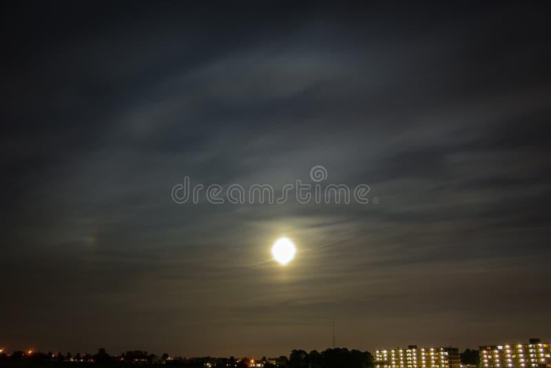 Яркий круговой венчик вокруг луны с parhelium к левой стороне стоковое изображение