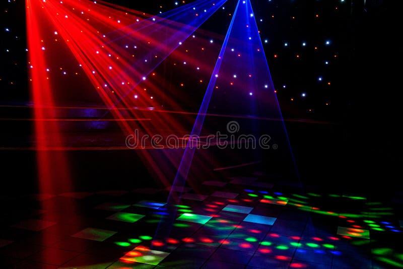 Яркий ночной клуб красный, зеленый, пурпурный, белый, пинк, голубые лазерные лучи режа через дым машины дыма делая свет и радугу стоковое фото rf