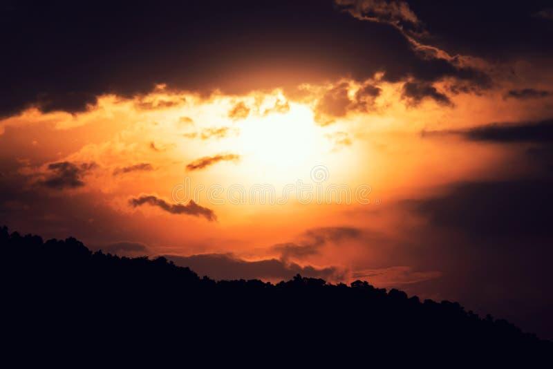Яркий оранжевый выравниваясь заход солнца Деревья силуэта между заходящим солнцем темное небо с двигая облаками Рассвет над горам стоковые фотографии rf