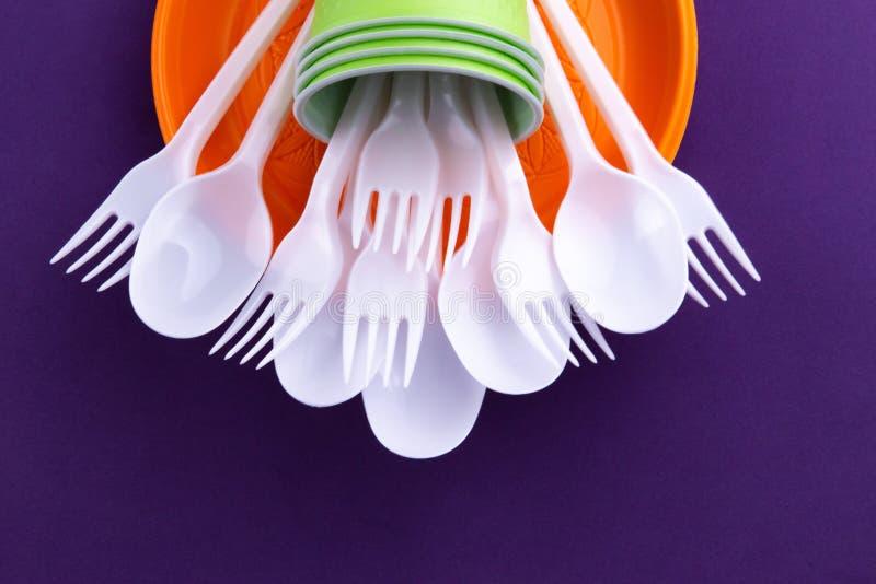 Яркий оранжевый и зеленый набор устранимого пластикового tableware на пурпурной предпосылке Проблема экологичности Отсутствие пла стоковое изображение rf