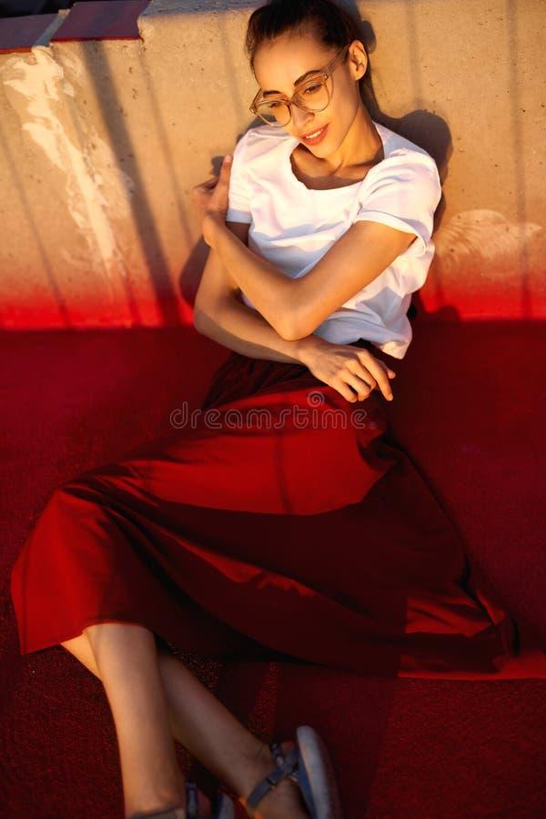 Яркий портрет образа жизни лета молодой милой женщины в eyewear, красной юбке и белой футболке, лежа на ярком красном цвете стоковое фото rf