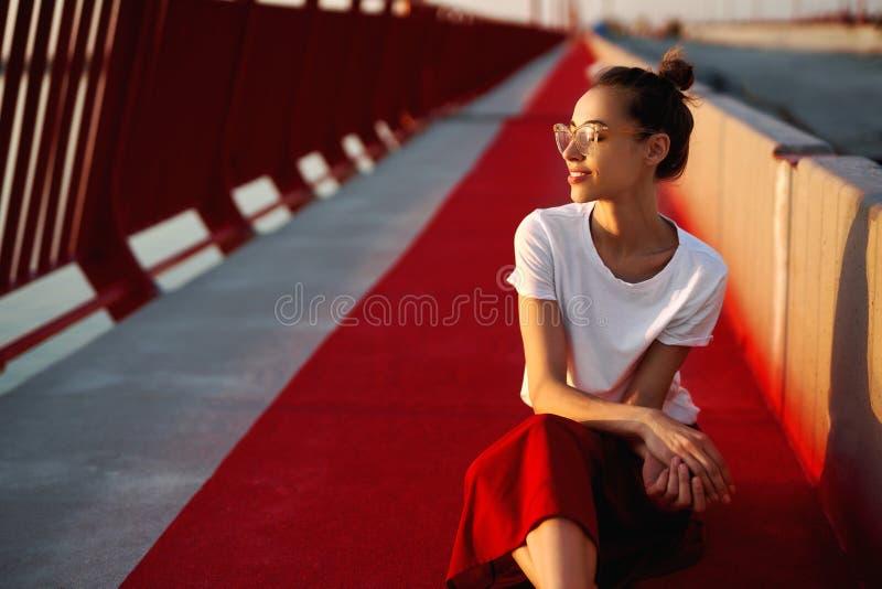 Яркий портрет образа жизни лета молодой милой женщины в eyewear, красной юбке и белой футболке, сидя на ярком красном цвете стоковые изображения rf