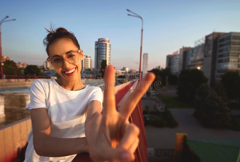 Яркий портрет образа жизни лета молодой милой женщины в eyewear, красной юбке и белой футболке, показывая знак мира с стоковые фото