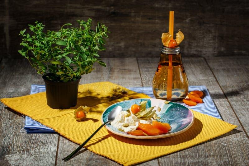 Яркий состав круглой плиты, оранжевой бутылки, и зеленого китайского дерева Милый комплект обедающего на деревянной предпосылке стоковое фото