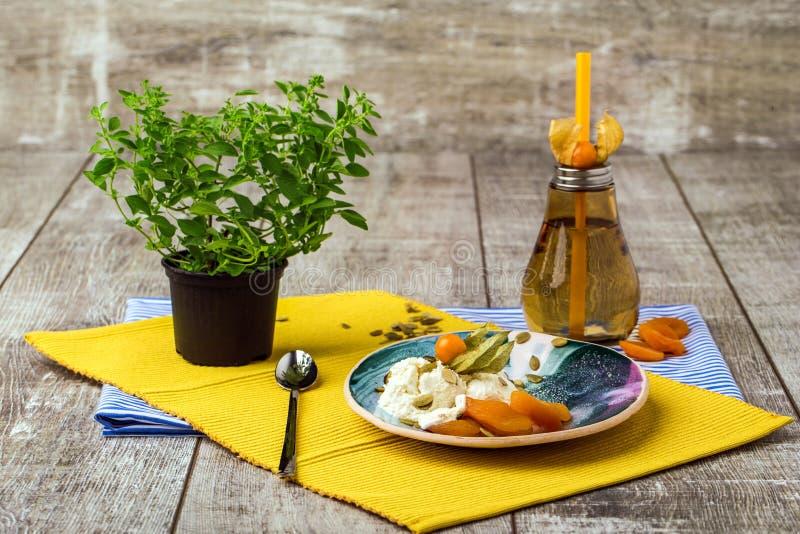 Яркий состав круглой плиты, оранжевой бутылки, и зеленого китайского дерева Милый комплект обедающего на деревянной предпосылке стоковые изображения rf