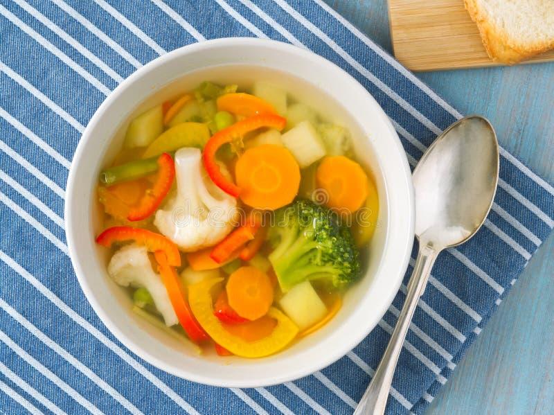 Яркий суп весеннего овоща с цветной капустой, брокколи, перцем, морковью, зелеными горохами Взгляд сверху, голубая деревянная пре стоковые фотографии rf