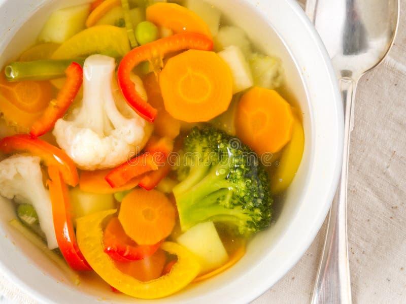 Яркий суп весеннего овоща с цветной капустой, брокколи, перцем, морковью, зелеными горохами Взгляд сверху, белая деревянная предп стоковое фото
