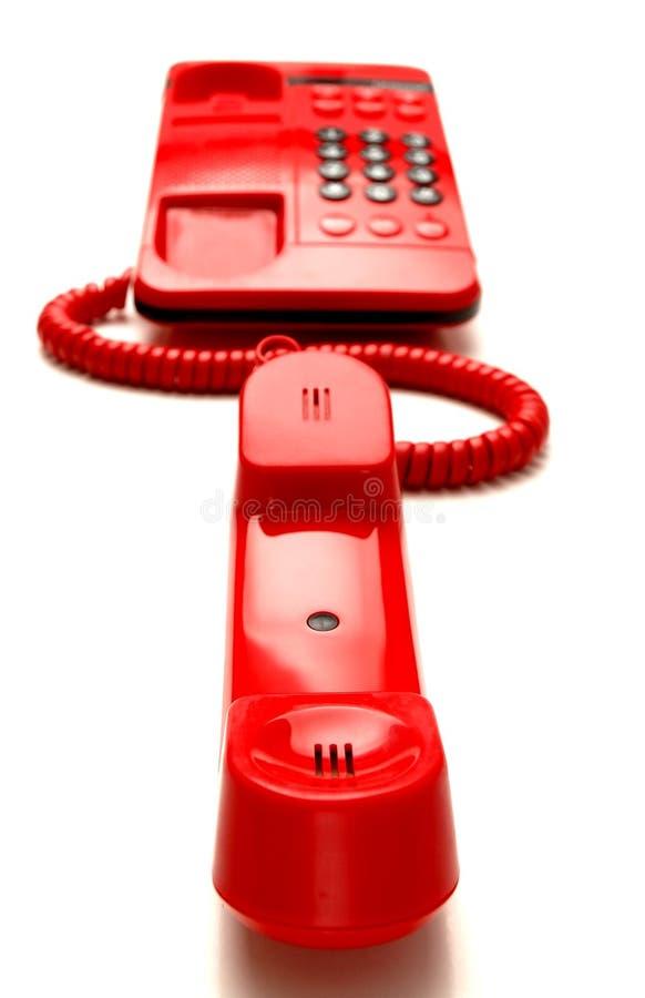 яркий телефон красного цвета настольного компьютера стоковые фотографии rf