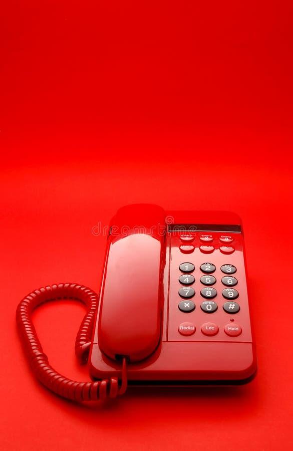 яркий телефон красного цвета настольного компьютера стоковое изображение