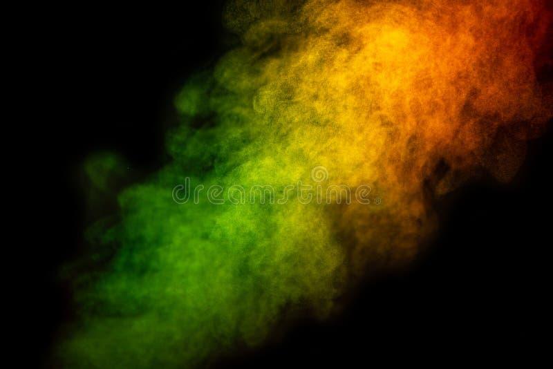 Яркий ый-зелен и желтый дым изолированный на черной предпосылке макрос стоковая фотография rf