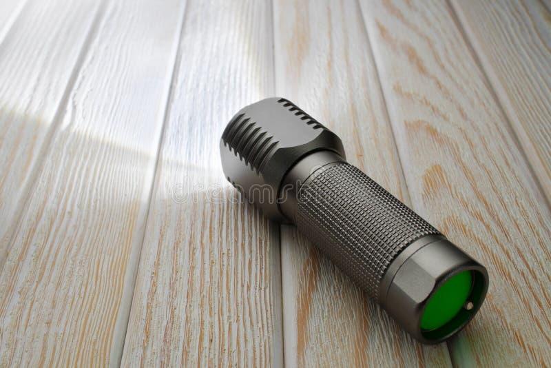 Яркий электрофонарь СИД светит на деревянной поверхности стоковое изображение