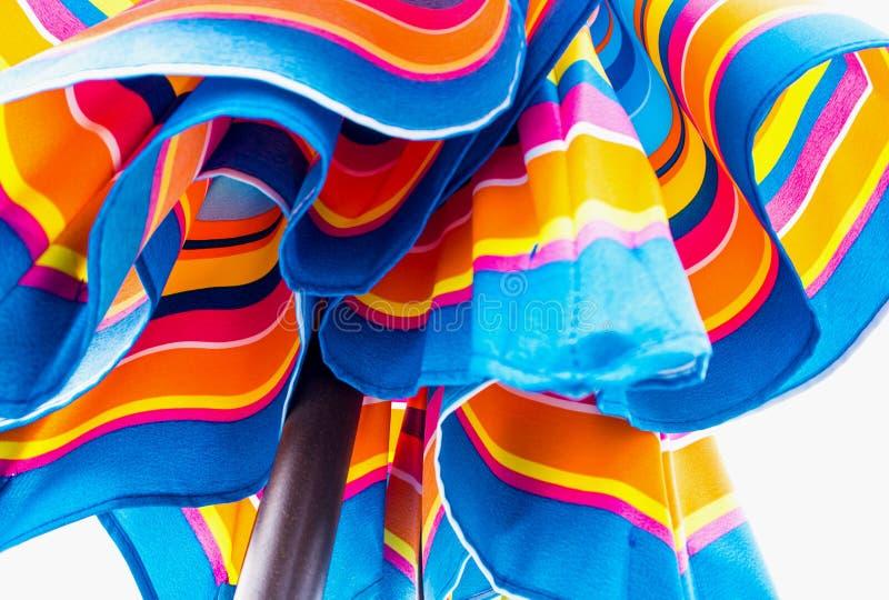Яркое голубое и апельсин зонтика пляжа стоковое фото rf