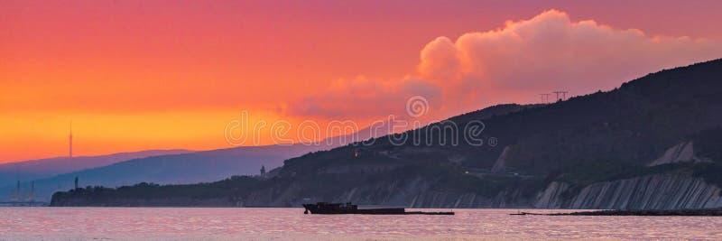 Яркое красное небо захода солнца над городом и горами стоковые изображения