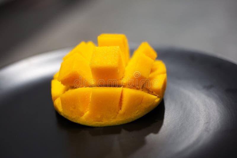 Яркое оранжевое манго на черной плите стоковое изображение