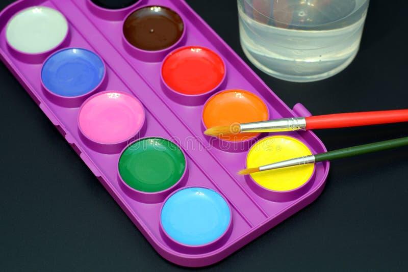 Яркое watelcolor красит в пластиковой коробке, щетках и стекле воды на темном - серая предпосылка стоковые изображения rf