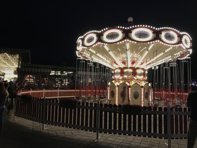 Ярко загоренный круговой carousel на обваловке Казани на вечере лета Люди едут на carousel и идут вокруг стоковые изображения rf
